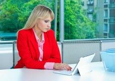 可爱的白肤金发的妇女在有膝上型计算机的办公室 免版税库存图片