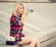 可爱的白肤金发的妇女坐木地板和拍摄与玩具照相机 免版税库存照片