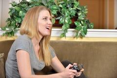 可爱的白肤金发的妇女打电子游戏 库存照片