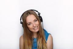 年轻可爱的白肤金发的妇女特写有佩带大黑专业监视耳机的逗人喜爱的微笑的反对白色演播室 库存照片