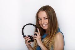 年轻可爱的白肤金发的妇女特写有佩带大黑专业监视耳机的逗人喜爱的微笑的反对白色演播室 免版税库存照片