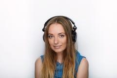 年轻可爱的白肤金发的妇女特写有佩带大黑专业监视耳机的逗人喜爱的微笑的反对白色演播室 免版税库存图片