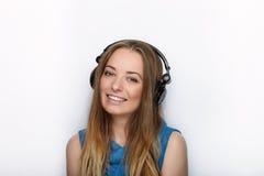 年轻可爱的白肤金发的妇女特写有佩带大黑专业监视耳机的逗人喜爱的微笑的反对白色演播室 库存图片
