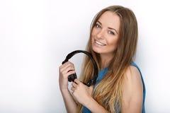 年轻可爱的白肤金发的妇女特写有佩带大黑专业监视耳机的逗人喜爱的微笑的反对白色演播室 图库摄影