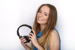 年轻可爱的白肤金发的妇女特写有佩带大黑专业监视耳机的逗人喜爱的微笑的反对白色演播室 免版税图库摄影