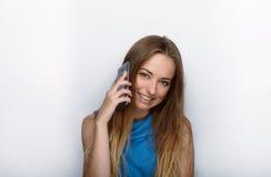 年轻可爱的白肤金发的妇女特写有逗人喜爱的微笑的在发短信在她的智能手机的白色背景 免版税库存照片
