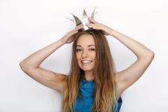 年轻可爱的白肤金发的妇女特写有逗人喜爱的微笑的在白色背景的手工制造公主冠 免版税库存照片
