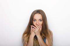 年轻可爱的白肤金发的妇女特写盖她的在白色背景的嘴 库存图片