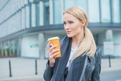 可爱的白肤金发的妇女站立的饮用的咖啡 免版税图库摄影
