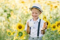 可爱的白肤金发的小孩男孩滑稽的吃百吉卷和饮用奶在夏天向日葵调遣户外 库存图片
