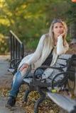 可爱的白肤金发的少妇坐一条长凳在公园 库存图片