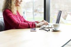 可爱的白肤金发的少妇播种的射击,在咖啡店键入坐黑屏膝上型计算机 卷曲白肤金发女性做自由职业者 免版税库存照片