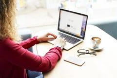 可爱的白肤金发的少妇播种的射击,在咖啡店键入坐黑屏膝上型计算机 卷曲白肤金发女性做自由职业者 图库摄影