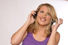 可爱的白肤金发的愉快的耳机妇女 免版税库存图片