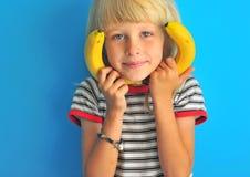 可爱的白肤金发的男孩画象用香蕉 免版税库存照片