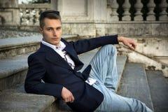 可爱的白肤金发的年轻人坐石台阶跨步外面 免版税库存图片
