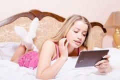可爱的睡衣白色袜子的女孩年轻白肤金发的妇女与片剂个人计算机计算机在说谎在白色床图片的手上 免版税图库摄影