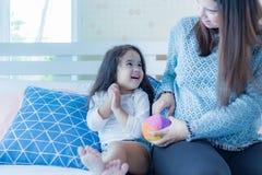 可爱的矮小的亚洲女孩或女儿看看充满爱的妈妈 做她的幸福和的学龄前儿童爱和母亲呆在一起 免版税库存图片