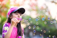 可爱的矮小的亚裔女孩吹的肥皂泡 免版税库存照片