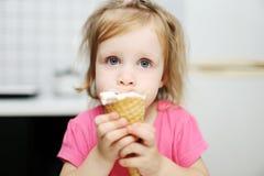 可爱的矮小的小孩女孩吃冰淇凌 库存图片