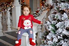 可爱的矮小的白肤金发的一件毛线衣的女孩小女孩有雪的 库存照片