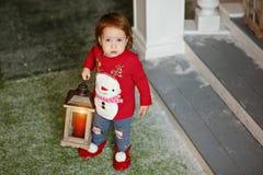 可爱的矮小的白肤金发的一件毛线衣的女孩小女孩有雪的 图库摄影