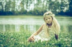 可爱的矮小的白肤金发的女孩在草甸 免版税库存图片