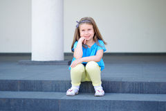 可爱的矮小的美丽的女孩坐楼梯 免版税库存图片