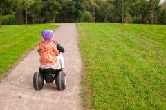 可爱的矮小的逗人喜爱的女孩乘坐摩托车 免版税库存图片