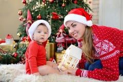 可爱的矮小的婴孩和母亲圣诞老人帽子使用的庆祝圣诞节,看照相机 新年` s假日 图库摄影