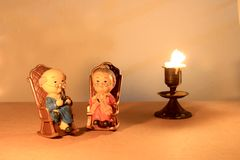 可爱的祖父母玩偶选址的经典椅子设计和蜡烛与轻的蜡烛定调子 低调照明设备,静物画样式 库存照片