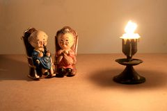 可爱的祖父母玩偶选址的经典椅子设计和蜡烛与轻的蜡烛定调子 低调照明设备,静物画样式 库存图片