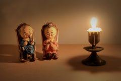 可爱的祖父母玩偶选址的经典椅子设计和蜡烛与轻的蜡烛定调子 低调照明设备,静物画样式 免版税库存照片