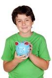 可爱的穿蓝衣的男孩moneybox 免版税库存图片