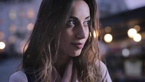 可爱的端庄的妇女看从照相机和微笑的边 特写镜头晚上与光的城市画象 股票视频