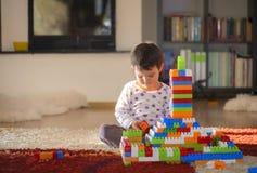 可爱的笑的小孩,使用与五颜六色的块的学龄前年龄的深色的女孩坐地板 库存照片