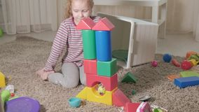 可爱的笑的小孩,学龄前金发碧眼的女人,使用与五颜六色的玩具,坐地板在屋子里 股票视频