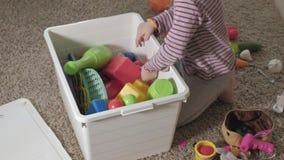 可爱的笑的小孩,学龄前金发碧眼的女人,使用与五颜六色的玩具,坐地板在屋子里 影视素材