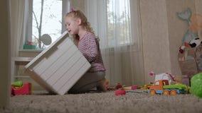 可爱的笑的小孩,学龄前金发碧眼的女人,使用与五颜六色的玩具,坐地板在屋子里 股票录像