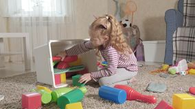 可爱的笑的小孩,学龄前金发碧眼的女人,使用与在白色箱子的五颜六色的玩具,坐在的地板 股票录像