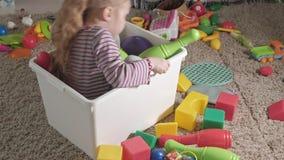 可爱的笑的小孩,学龄前金发碧眼的女人,使用与在白色箱子的五颜六色的玩具,坐在的地板 股票视频