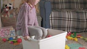 可爱的笑的小孩,学龄前金发碧眼的女人,使用与在白色箱子的五颜六色的玩具,坐在的地板 影视素材