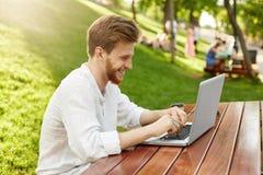 可爱的红头发人人画象有胡子的在白色衬衣,坐在公园,笑和做他的工作在膝上型计算机 免版税库存照片
