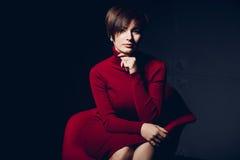 可爱的红色妇女 塑造一个性感的年轻企业夫人的画象一件红色礼服的在黑暗的背景 免版税库存图片