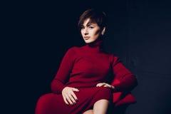 可爱的红色妇女 塑造一个性感的年轻企业夫人的画象一件红色礼服的在黑暗的背景 免版税库存照片