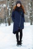 年轻可爱的红头发人妇女美丽的冬天画象在获得逗人喜爱的被编织的帽子的冬天在多雪的公园道路的乐趣 免版税库存图片