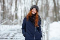 年轻可爱的红头发人妇女美丽的冬天画象在获得逗人喜爱的被编织的帽子的冬天在多雪的公园楼梯的乐趣 库存照片