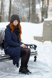 年轻可爱的红头发人妇女美丽的冬天画象在获得逗人喜爱的被编织的帽子的冬天乐趣坐长凳多雪的公园 免版税库存图片