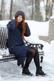 年轻可爱的红头发人妇女美丽的冬天画象在获得逗人喜爱的被编织的帽子的冬天乐趣坐长凳多雪的公园 免版税图库摄影