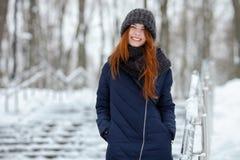 年轻可爱的红头发人妇女美丽的冬天画象在获得逗人喜爱的被编织的帽子的冬天在多雪的公园楼梯的乐趣 免版税库存图片